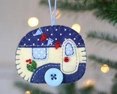 Felt trailer Christmas ornament. Vintage caravan trailer hanging ornament, handmade from felt and decorated with fabric scraps. With tiny felt bunting and buttons for the wheel and door knob. Available in vintage blue and cream, or vintage red and cream. Blanket stitched edges and