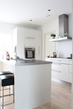 #5. All white kitchen with exposed hood, painted cabinets, aluminium plinth, island with place for breakfast.
