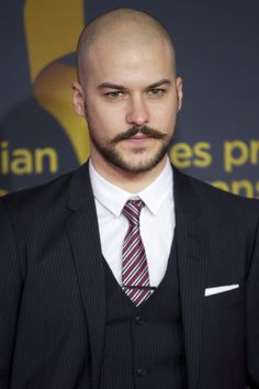 I'm not a bald and beard lover, but something about the shape of this clean, clean beard and that wide, wide moustache.  Ummh. Plus, I  love stern in a suit, daddy.