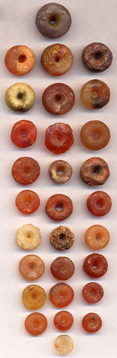 ca. 5,000 BCE. Neolithic stone beads from early settlements in Sahara, North Africa. Using simple hand-carved tools, stones were placed on a grooved stone and  pecked out from both sides which was difficult, nonetheless, modern means cannot duplicate them. Tubular beads were even more difficult and came later in the Bronze Age in West Asia and the Indus Valley. Holes are generally not smooth nor even. SItes show many beads were broken in the process.