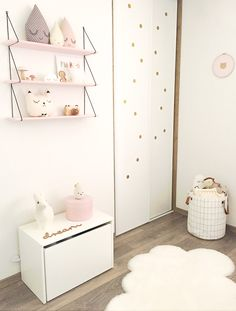 Chambre bébé douce : Une étagère, des peluches gouttes, un coussin chat et des pois dorés