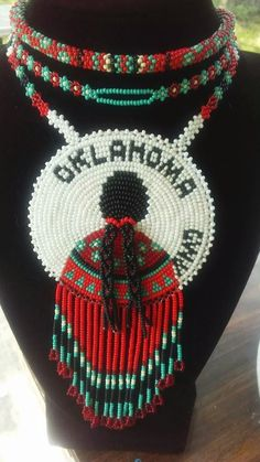"CHEROKEE national holiday art show 2017 award winning beaded medallion. This hand beaded medallion placed 2nd place in the cherokee national holiday art show, and is up for sale. Beautiful native Indian lady with ""OKLAHOMA,"" and ""CWY,"" pronounced tsa la gi -meaning ""CHEROKEE, "" this was hand beaded by artist Andrea Tidwell and is a one of a kind beautiful piece of jewelry and work of art. Leather backing, signed on the back, features one beaded daisy chain neckla..."