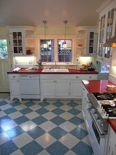 Newly remodeled retro kitchen on a rainy mid-morning day. The new cabinets mimic the house's original 1920's shaker style cabinets. The new floors are VCT (from Mannington) that have a look similar to linoleum. The floor colors are Almondine and Spruce. The counter top is Dupont's Zodiac synthetic quartz stone.