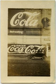 Vintage snapshot of classic Coca-Cola signs with antique car driving past.