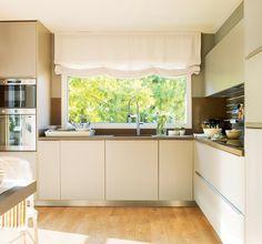 Cocina en L en tonos claros, con parquet de madera, amplias ventanas con estores y electrodomésticos en columna