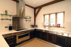 Dark wood kitchen cabinets with white semi gloss surfaces, stainless steel oven with electric hobs and stainless steel backsplash and hob hood above, dark stained oak frame.