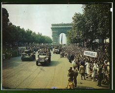 Crowds of French patriots line the Champs Elysees to view Allied tanks and half tracks pass through the Arc du Triomphe, after Paris was liberated on August 25, 1944