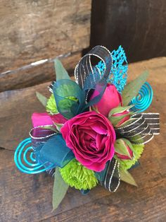 wrist corsage featuring hot pink spray roses, green button mums, seeded eucalyptus, black and teal ribbon, blue wire and blue glitter lead accent - $37.95 - http://www.leighflorist.com #prom #promflowers #wristcorsage #leighflorist