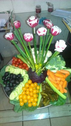 A veggie tray I made for the company Christmas party. The center piece is half of a purple cabbage with wooden BBQ sticks, covered in green onion topped with radishes that were cut like roses (put them in ice water overnight so they open). On the side I had cut different colored bell peppers in half and filled them with dips for the veggies