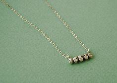 Tiny sterling silver skull necklace. $64.00, via Etsy.
