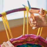 With a hula hoop or embroidery hoop for a loom, you and your kids can weave unwanted T-shirts into a rug!