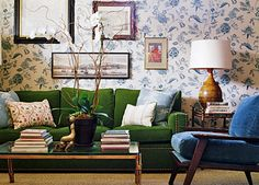 Colorful living room with green couch with nailhead detail, blue side chair, blue and white patterned wallpaper.