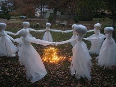 Lawn ghosts (made from inexpensive plastic drop cloths) dance around the fire (a bunch of warm - don't use cool - white Christmas lights) for a very scary look that's easy to create. DIY instructions.