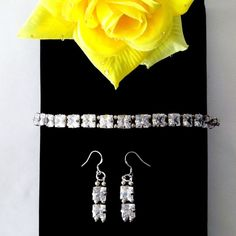 The White Princess 8 inch tennis bracelet and 1.75 inch earring set features a series of 3 carat faceted square cut white Cubic Zirconia with sterling silver embellishments and findings.