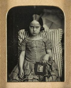 """""""She's thrilled. THRILLED. Unknown little girl sitting on a striped cushion holding a framed portrait of a man, possibly her dead father, by Ross & Thomson of Edinburgh,1847-60, ninth-plate daguerreotype. National Museums of Scotland."""""""
