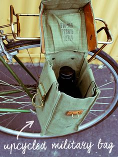 Originally used by the Belgian Army to hold a gas mask, this vintage bag has been refashioned into a handy carrier for growler bottles on bike. Simply snap on the leather loops to your back bike rack and pack in your precious cargo for the ride home. Plus, the shoulder strap tucks all the way in and out of the way when you're riding. The bike pannier bag also fits bottles of wine, to port your pinot.