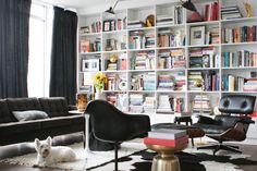 "Linda Derschang had the floor-to-ceiling shelves installed to store her ample book collection. ""I love to sit here, and see downtown, and read,""  she says. Credit: Heather Keeling (ApartTherapy.com)"