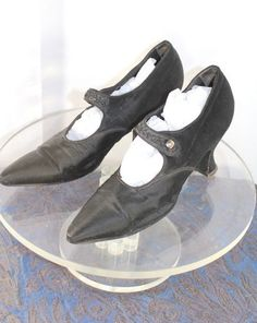 "Circa 1920 black silk evening or dress shoes are an elegant mix of late teens and early 20s features: An elongated toe, but with a curvy Louis heel and beaded Mary Jane strap.  The ½"" wide strap fastens with a grey mother button, and are decorated in a foliate motif with faceted jet glass beads. Typical of dress shoes in this period, the silk fabric covers a leather base except for the pointed toe, which is backed in a sturdy white faille. Shoe sole and sockliner are both black leather."