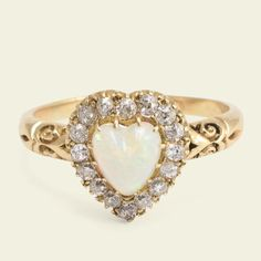 This sweet Victorian ring is fashioned in 18k yellow gold. The head of the ring is modeled in the formof a heart and set with a colorful opal cabochon and 16 old mine cut diamonds. The shoulders are chased with a classic late Victorian scroll motif witha shuttle-shaped cleft where they meet the half round hoop.    Materials: 18k yellow gold, 6.2mm x 7mm opal heart cabochon, 16 old mine cut diamonds approximately .03ct each  Age: c. 1880  Condition: Excellent  Size: US 8.5, can be…