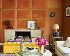 Wall Treatment Design Ideas - Decorator Nate Berkus updated his historic Chicago home's original oak-paneled walls with handsome leather inserts; a custom-made ottoman upholstered in a cheery Clarence House cotton velvet lends a colorful note in front of the coquina fireplace.