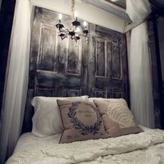"""old reclaimed wood door repurposed as a headboard with a hanging chandelier. great idea!  (from """"Tuesday Trendspotting: Unique Headboards"""