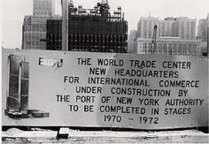 A sign tells visitors what to expect. THE WORLD TRADE CENTER NEW HEADQUARTERS FOR INTERNATIONAL COMMERCE  UNDER CONSTRUCTION BY THE PORT OF NEW YORK   AUTHORITY TO BE COMPLETED IN STAGES 1970-1972.
