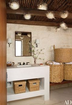 The pool bath of a Laguna Beach, California, home conceived by KAA Design and Atelier AM features porcupine fish dangling from the ceiling, while round baskets from Mecox provide storage for towels.