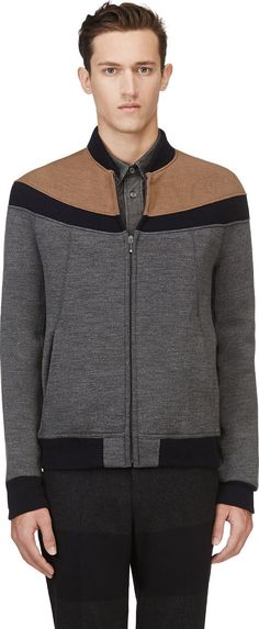Zip-up bomber jacket in grey wool. Navy stretch wool trim throughout. Brown wool panels at exterior. Side slit welt pockets. Unlined. Tonal stitching.