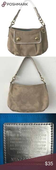 """Coach Small Shoulder Purse Monogram Handbag Authentic Coach purse with beige & tan logo monogram and gold hardware. No. K0972-13833.  Adorable front pocket with snap closure and gold button details. Silver leather strap and bright blue lining.   Pre-loved item with some wear from normal use. Watermark on front pocket (shown in 4th photo), and abrasions in the gold hardware rings near the strap (shown in last 2 photos).   11.5"""" wide (across the middle).  8"""" height from zipper to base…"""