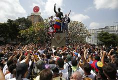 Venezuela's opposition leader Leopoldo Lopez (holding flag), wanted on charges of fomenting deadly violence, stands on a public monument dur...