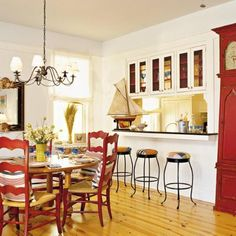 White kitchen with red chairs and grandfather clock | SouthernLiving.com