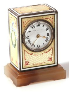 Rectangular, beautifully decorated with laurel wreaths and bows on sides and a burgandy design on front and top all on a background of yellow guilloche enamel. The dial is white enamel with black Roman numerals