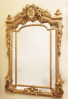 A  French 19th Century Louis XV Style Gildwood Carved and Gesso Figural Mirror Frame. The upper cresting carved with a pair of Putti holding foliate and flanking a ribbon-tied center medallion with a portrait of a Royal Maiden. The foliate-carved sides with classically-draped figures of maidens terminating in scrolled corners, the lower panel section centered with a cherub mask. Circa: Paris, 1880  Height: 75 inches (130.5 cm) Width: 50 1/4 inches (127.6 cm) from Jan's & Company