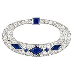 Art Deco Platinum, Diamond and Sapphire Brooch, Cartier   The openwork tapered oval brooch topped by one square-cut sapphire, accented by 3 diamond-shaped sapphires spaced by 2 round sapphires, set throughout with 66 old European and single-cut diamonds approximately 3.05 cts., and 4 rose-cut diamonds, signed Cartier, no. 1399, circa 1920.