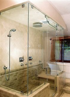 Handheld Shower Head attached directly to the glass wall.