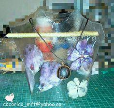 Presentoir à collier, fait d'une bouteille de plastique. Des fleurs naturelles sont collées au modpodge à l'interieur.  Pas trop mal :-)