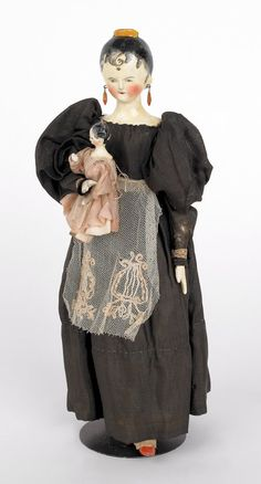 Early carved and painted wooden mother with baby doll, ca. 1800, with original hand sewn clothing, 11'' h.