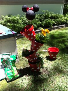 Painted terra cotta pots with painted styrofoam balls to look like Minnie Mouse stacked on rebar. Mom stacked the pots and planted the flowers.