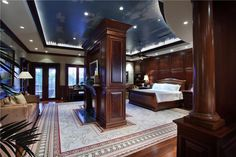 Enormous master bedroom with extensive wood paneling with matching custom bed. Partition wall with fireplace creates separate sitting area