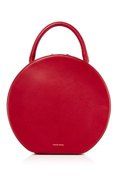 Combining understated refinement with exacting Italian craftsmanship, **Mansur Gavriel** have established themselves as the bags of desire amongst the fashion elite. Crafted from burgundy calf leather, this Mansur Gavriel circle bag serves up sophisticated style with minimal fuss.