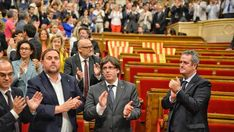 The members of the Catalan Government celebrate the result of the vote that endorses the declaration of independence in the parliament. The empty seats on the right were left by the members of the unionist parties who refused to vote as a sign of protest.