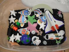 "Space Discovery Bin: contains black beans, glow in the dark stars, Styrofoam stars, space foamies, little lego astronauts, white ""moon"" rocks, earth stress ball, and toy rocket ship"