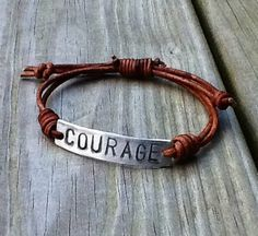 I hand stamped the word COURAGE onto a solid non tarnish Pewter metal and attached distressed brown leather that closes with a sliding knot closure