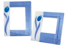 "Murano glass fusing photo frame. Elegant composition featuring a stylized floral motif and sinuous lines. The combination of white and blue glass gives to the object a highly refined effect. This object is made entirely by hand and is therefore a unique piece, it can thus submit variations in color shades and in choosing the type of ""murrine"", depending on availability and composition. This guarantees the originality and quality of craft product Made in Italy."