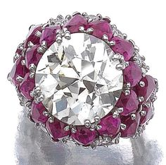 Ruby and diamond ring, Bulgari.   Centring on a circular-cut diamond weighing 10.55 carats, to a mount enhanced with pear-shaped rubies and brilliant-cut diamonds, mounted in white gold, size 54, signed Bulgari. Sotheby's.