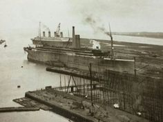 October 1911, Titanic under construction while Olympic returns to Belfast for repairs after her collision with HMS Hawke.