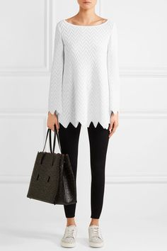 ALAÏA Zigzag knitted tunic $3,150 Completely unique to the brand, Alaïa's knitted fabrics have been developed over many years with a factory in Italy. This tunic is spun with a graphic zigzag pattern - accentuated by the cut of the hem - and has flared sleeves. Offset yours with skinny pants or leggings. Shown here with: Alaïa Leggings, Alaïa Tote, Alaïa Sneakers.