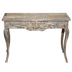 19th Century French Provencal Console  France  19th Century  19th Century French Provencal Console, rustic and worn, with earlier gilded finish still remaining on carvings. The top has a molded edge and rests on a square apron with a decorative cartouche in the center. Beneath, four cabriole legs extend into hoof feet.