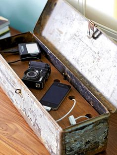 An antique toolbox repurposed for a modern necessity: Charging devices. Drill a hole in the side of a toolbox large enough to feed an electrical plug through. Place a plug strip inside the box; feed the plug through the hole. Cut a board to fit inside the box and drill holes on the board (large enough so that one end of your charging cords can feed through them).