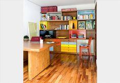 As diferentes cores da laca desta estante ajudam a identificar os livros, separados por temas. Como o móvel já tinha visual exuberante, no lugar de puxadores, a arquiteta Daniela Almeida achou melhor fazer furos redondos nas gavetas e nas portas